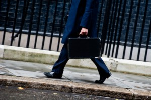 A businessman walks holding a black briefcase